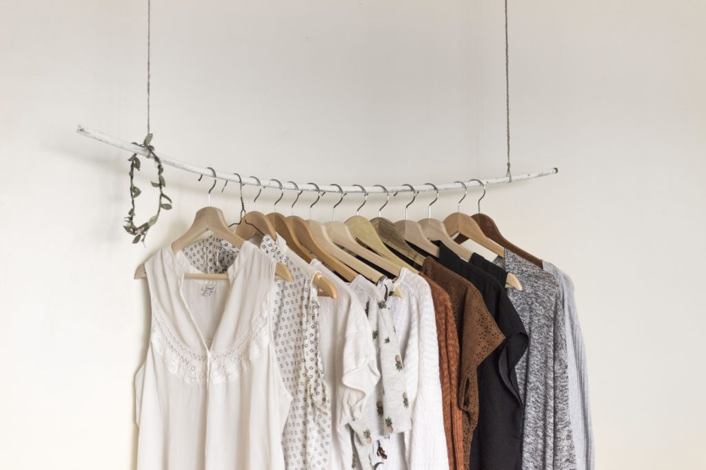 Against a white background, thirteen wooden hangers with women's clothing rest on a white metal rod suspended from the ceiling by two pieces of steel wire.