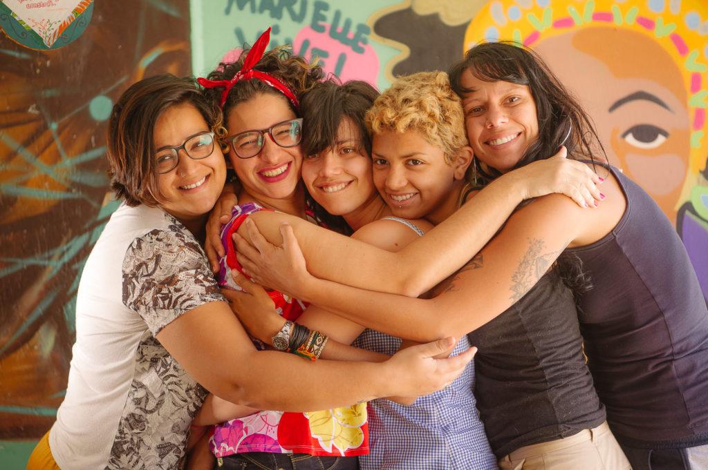 Cinco mujeres están de pie y se dan un abrazo firme, sonriendo para la foto. Todas son blancas y tienen ojos oscuros, cuatro tienen pelo oscuro y una tiene pelo rubio corto. Tres mujeres tienen cabello lacio y dos, rizado. Usan blusas mangas corta o sin mangas. En el fondo, hay una pared con un graffiti colorido.