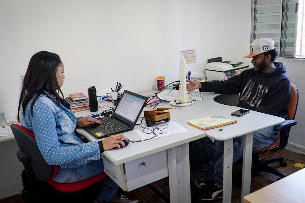 Una habitación blanca con una mesa, el mismo hombre de la imagen 1 está sentado en una silla naranja frente a una computadora blanca. Del otro lado de la mesa, una mujer con pelo lacio y blusa de jeans con lunares blancos sentada en una silla roja está usando su laptop negro. Encima de la mesa también hay materiales como tazas, papeles e impresora.