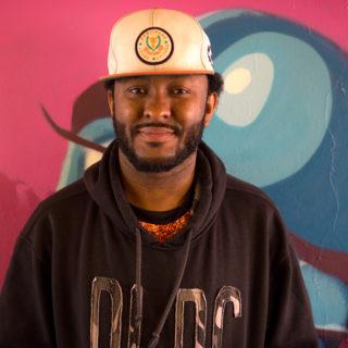 Un hombre de piel negra y de barba, posa mirando a la cámara. Viste sudadera negra con letras bordadas, una gorra blanca con un logotipo. En el fondo, un graffiti de color rosado y tonos de azul.