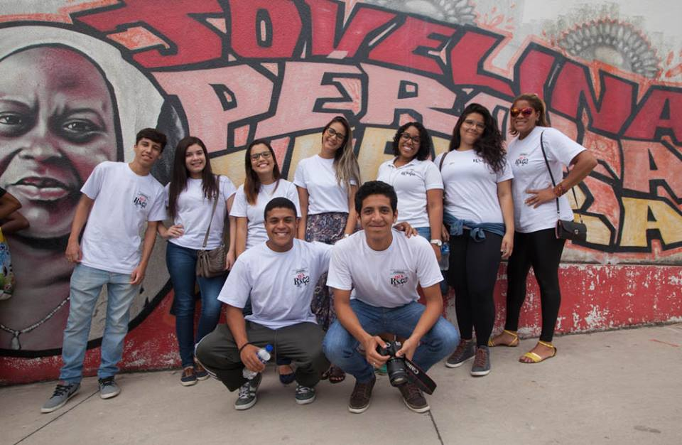 "Nine youngsters smile at the camera while posing against a colorful mural, all wearing a white t-shirt with the ""Fala Roça"" logo printed on the left side. Two young men are crouching in front. The one of the left has his arm around the one on the right, who is holding a camera. Behind them is a young man on the left and six girls next to him, all in a row"