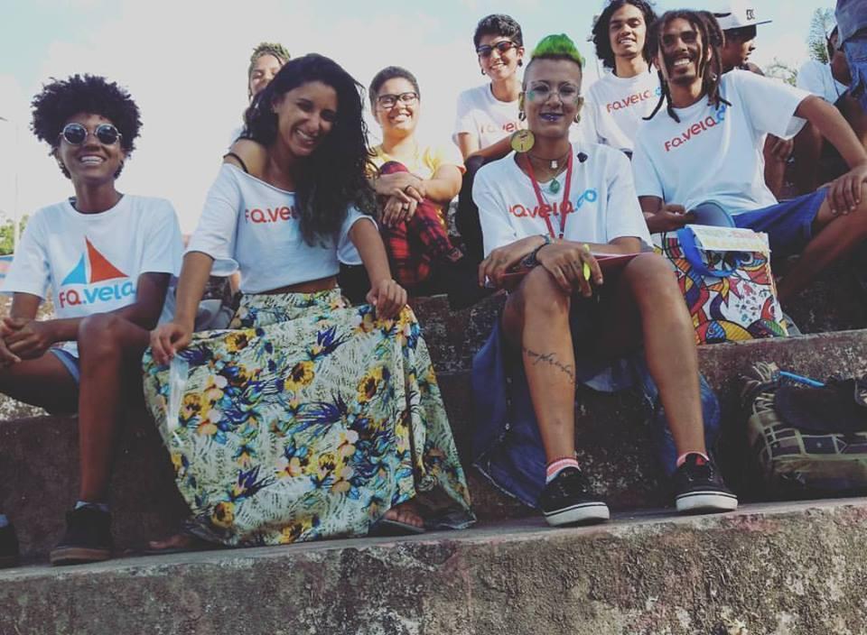 Um grupo de nove jovens, integrantes do FA.VELA, usam camisetas com o logo do grupo. Eles estão sentados em uma escada e sorriem para a foto.