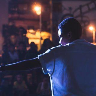 Uma mulher negra se apresenta para uma plateia em um evento à noite. Na imagem, ela está contra a luz, quase totalmente de costas para. Ela tem os cabelos curtos, usa uma camisa clara de manga curta larga e olha para o lado esquerdo, com o braço esticado apontando para fora da imagem. No fundo, que está desfocado, diversas pessoas estão sentadas em uma espécie de arquibancada pequena, olhando para a mulher. Também há dois postes de luz.