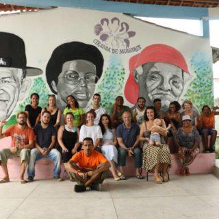 Aproximadamente 20 personas están sentadas en dos escalones, mirando a la cámara. Hay hombres, mujeres, y un bebé en brazos. En la pared de detrás hay tres dibujos: un señor con bigote y sombrero negro; una mujer negra con gafas y una señora mayor negra con un pañuelo rojo recogiendo su pelo.