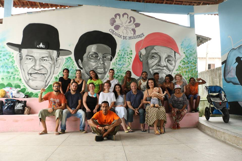 Approximately 20 people are sitting on two steps under a lofted roof, looking at the camera. There are men, women and a baby. On the wall behind them are three drawings: an old man with a moustache and a black hat; a black woman wearing glasses; and an old black woman wearing a red bandana.