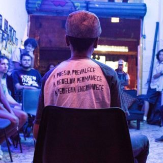 "On the foreground is a young black man, sitting with his back to the camera, wearing a t-shirt with the phrase ""Poetry prevails. Rebelliousness remains. The periphery grows."" written in Portuguese. He is wearing a pink cap and is facing a circle of people in a space lit by a blue light and with many photographs on the wall. The people are all looking at the young man."