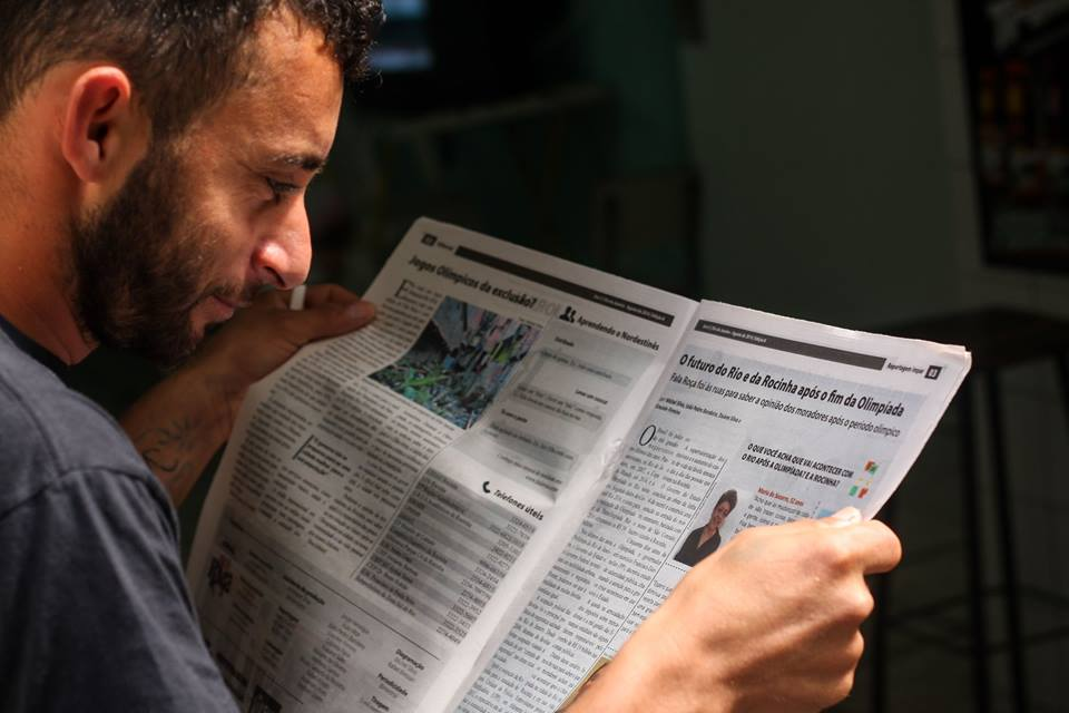 A white skinned man with a beard and wearing a gray t-shirt is seen from the side reading a newspaper.