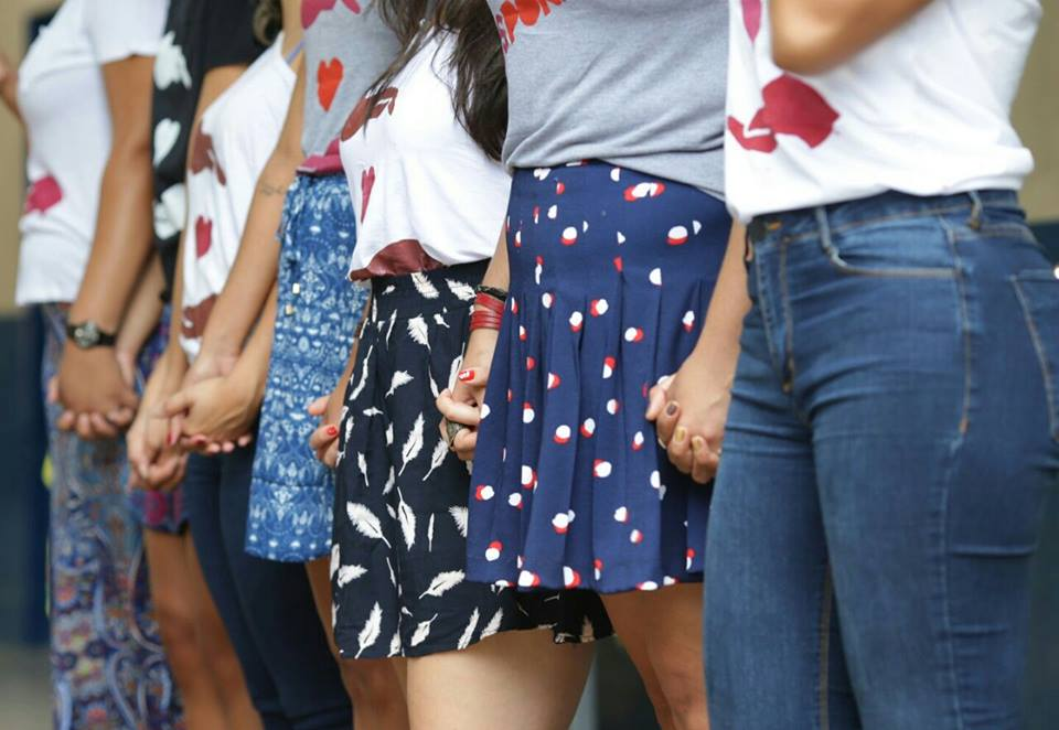 Seven women are standing side by side, holding hands. The photo is from their waist down. They are wearing the same t-shirt, and five of them are wearing skirts and two are wearing jeans.