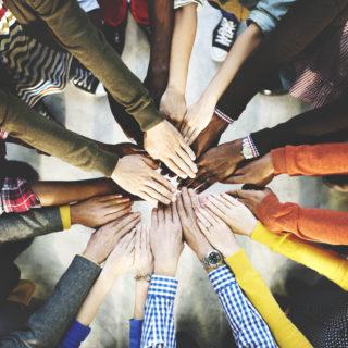 Mãos de diversas pessoas estão juntas, uma em cima da outra.