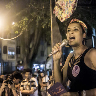 In the foreground, on the right side of the photo, a black woman holds a microphone to her mouth. She is wearing a black tank top and is holding a stack of purple flyers and has a round purple sticker on her shirt. She is in an open space in the street at night. The background is out of focus, and there are people watching her and taking photos.