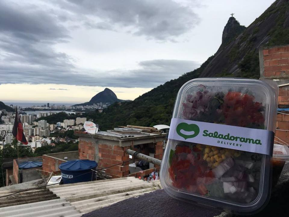 In the foreground of the photo, to the right, is a clear plastic container. Inside are a variety of fresh foods. Behind it are houses of a favela in Rio de Janeiro. Further back is a bay and hills, with the Corcovado mountain and the Christ the Redeemer statue.