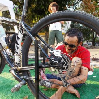 The photo's foreground is taken up by a bicycle wheel resting on the ground. It is the back wheel of a bicycle, and behind it a white skinned man is smiling and cleaning its chain. He is sitting on the ground, with one of legs folded up. He has short black hair and is wearing sunglasses, a red t-shirt, blue shorts, and is barefoot.