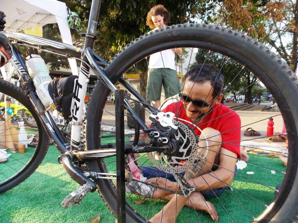 Em primeiro plano, está a roda de uma bicicleta apoiada ao chão. Só está enquadrada a roda de trás e, atrás do aro, um homem branco sorri e mexe na correia da bicicleta. Ele está sentado no chão, com uma das pernas dobradas. Ele tem cabelos curtos pretos, usa óculos escuros, camiseta vermelha, uma bermuda azul e está com os pés descalços.