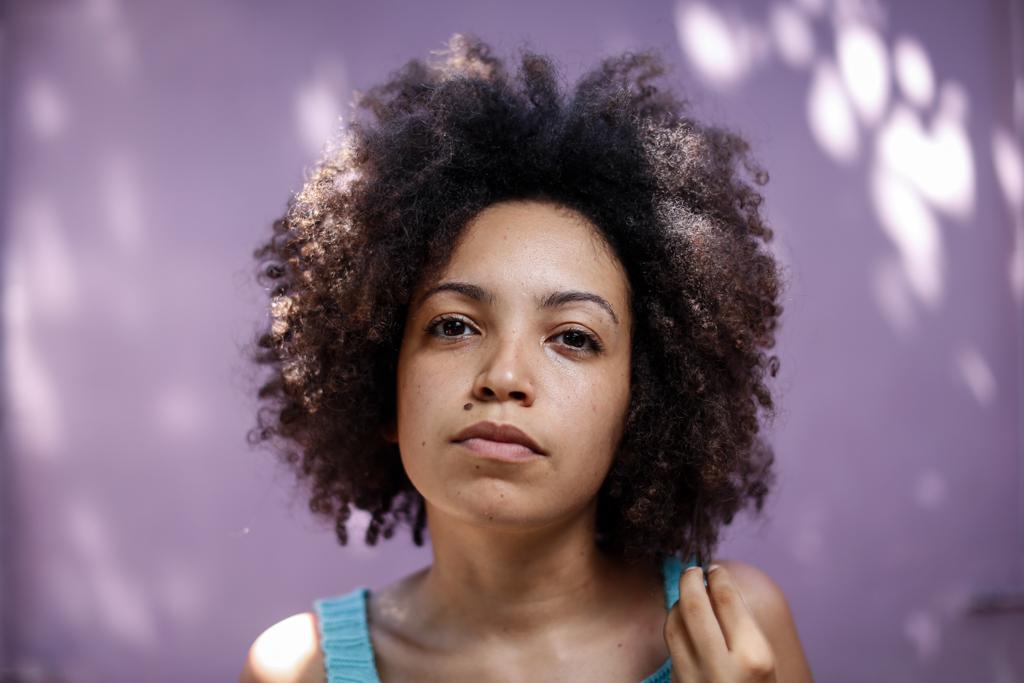 Uma mulher negra posa para a foto, olhando para frente. É possível ver uma parte do tronco e a cabeça. Ela segura uma mecha do cabelo e a estica. Ela veste uma blusa regata azul clara. Ao fundo, há uma parede roxa, com algumas manchas de sol.