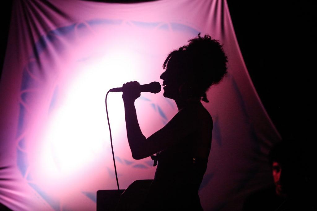 La sombra de una mujer de costado sosteniendo un micrófono cerca de la boca. En el fondo, se extiende un paño rosado, con una clara luz fuerte en el medio.
