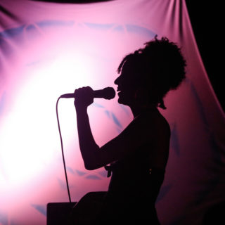 A sombra de uma mulher de lado segurando um microfone perto da boca. Ao fundo, um pano rosa está esticado, com uma luz forte clara ao meio.