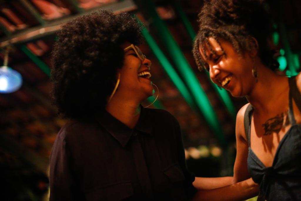 Duas mulheres negras riem uma para a outra. A mulher da esquerda tem os cabelos soltos, usa brincos de argola, óculos e uma camisa fechada preta. A da esquerda tem parte do cabelo preso e a franja está solta, usa brincos e uma blusa regata preta. Ela tem uma tatuagem na altura do tórax.