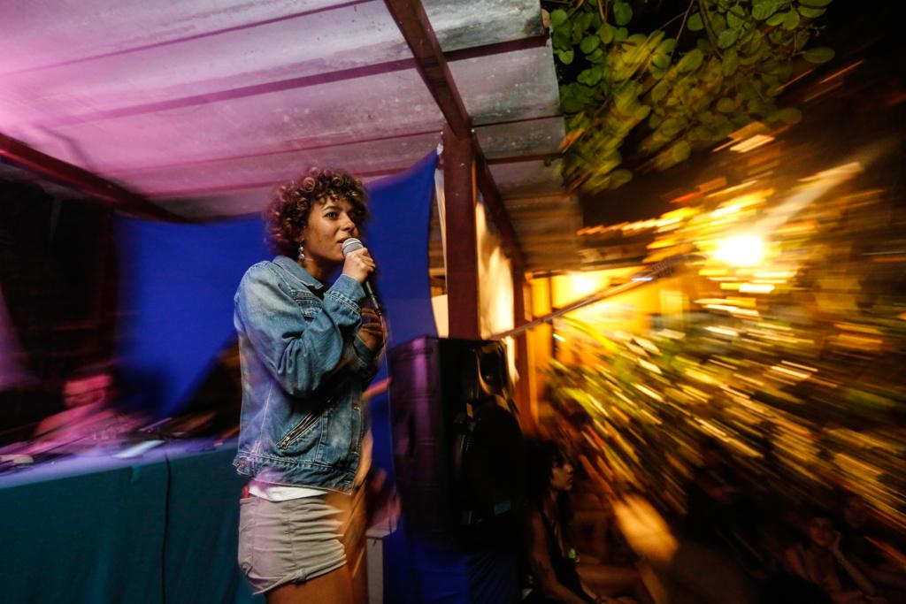 Uma mulher negra e cabelos curtos se segura o microfone durante uma apresentação de slam. Ela está de jaqueta jeans e um shorts claro. O fundo está desfocado, passando a ideia de movimento, com mistura de luzes, branca e rosa, na composição da imagem.