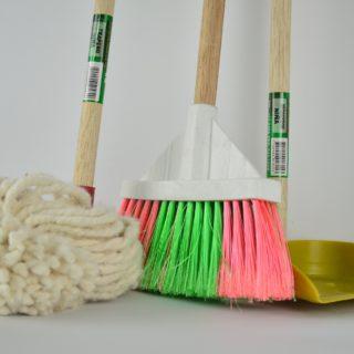 Imagem de fundo branco com a parte inferior de um esfregão branco, à esquerda, de uma vassoura com franja rosa e verde, ao meio, e uma pá de plástico cor dourada à direita. Todos possuem cabo de madeira.