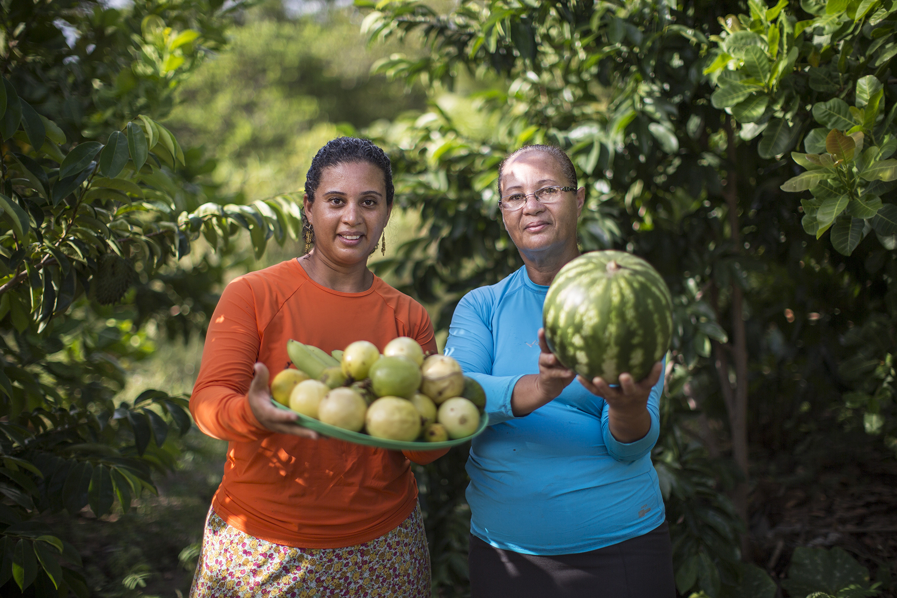 Two women side by side, surrounded by dark green leafy bushes and trees. The woman on the left has dark eyes and dark hair and wears an orange blouse with a printed skirt. She holds a tray with a variety of fruits. Next to her is a lady with white hair wearing glasses and a blue blouse with a black skirt. The older woman holds a medium-size watermelon.