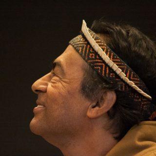 Un señor de origen indígena está de perfil para la cámara, mirando hacia arriba con una sonrisa. Aparece solamente el cuello y la cabeza, entre la frente y el pelo, tiene una tira en la frente, como si fuera una faja. El fondo es oscuro y sin ningún elemento.