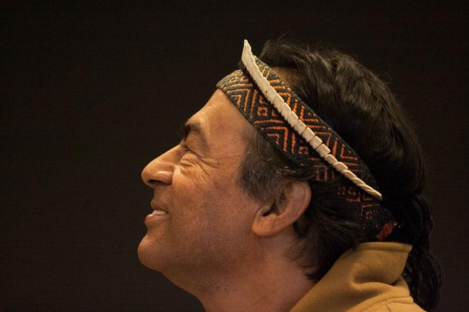 Um senhor de origem indígena está de perfil para a câmera, olhando para cima, com uma expressão de sorriso. Aparece só o pescoço e a cabeça, entre a testa e o cabelo, o senhor uma um objeto preso, como se fosse uma faixa. O fundo é escuro e sem nenhum elemento.