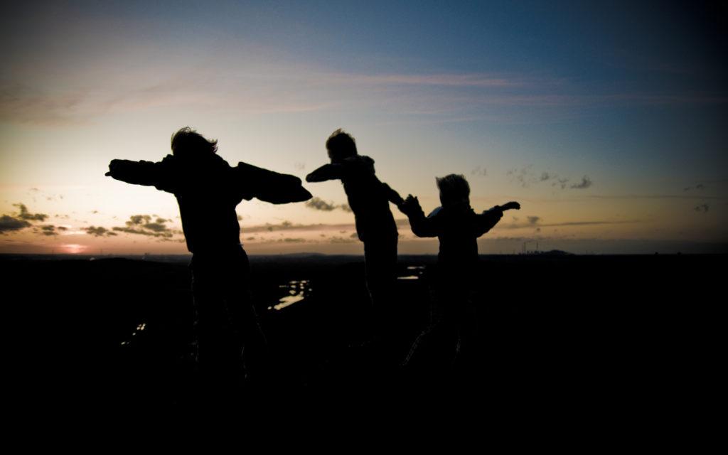 Silueta de tres niños de la mano corriendo juntos por un campo (que también aparece su sombra). En el fondo la imagen, un amanecer