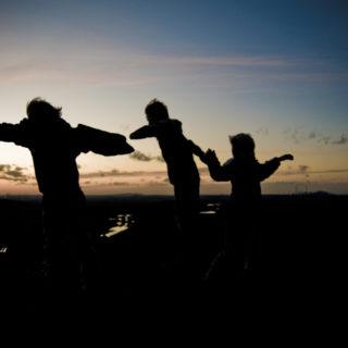 Silhueta de três crianças de mãos dados correndo juntas por um campo (que também aparece em sombra). Ao fundo a imagem de um nascer do sol