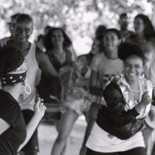 Foto em preto e branco, onde um grupo de mulheres negras enfileiradas lado a lado estão dançando, . Outra mulher negra, de cabelos amarrados com um lenço, está de costas para a imagem e de frente para o grupo, em primeiro plano, e ensina passos de dança a estas mulheres.