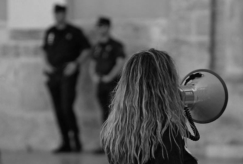 Foto em preto e branco de uma mulher de cabelos loiros e longos, de costas para a câmera, falando por um megafone. Ao fundo, imagem desfocada de dois policiais em guarda.