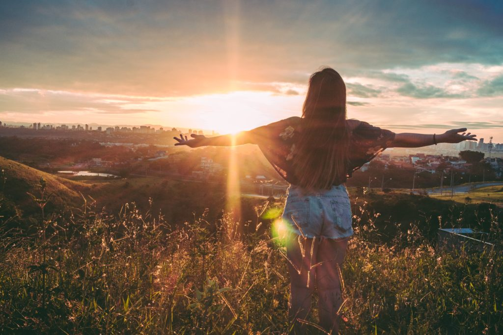 A young woman with long, dark hair, her back to the camera, stands on a hill looking at the sunset, her arms wide open. She wears a flowered blouse and cutoff denim shorts. There is a city on the horizon, and many clouds in the sky.