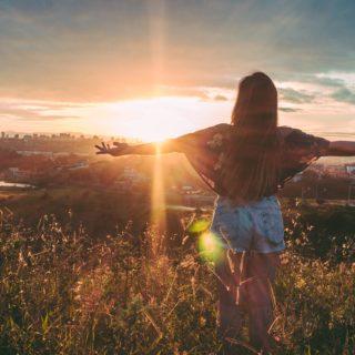 Una joven de cabello oscuro y largo, usa una blusa florida y un short de jean y está de espaldas a la imagen, con los brazos abiertos. Está encima de una colina, mirando la puesta del sol. En el fondo, hay una ciudad. El cielo es naranja, la luz del sol es fuerte y hay muchas nubes.