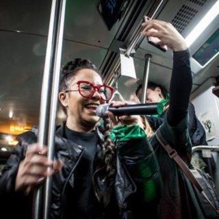 Un grupo de personas está dentro de un vagón del metro. La foto, tomada desde abajo, muestra a una mujer blanca que usa gafas con armazón rojo, con cabello oscuro atado, vistiendo una blusa oscura y, encima, una chaqueta negra. Ella está girada ligeramente a la izquierda y sonríe. Tiene un pañuelo verde atado en su brazo izquierdo. Alrededor hay otras personas.