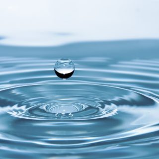 Close up of a drop of water falling in blue water, making ripples.