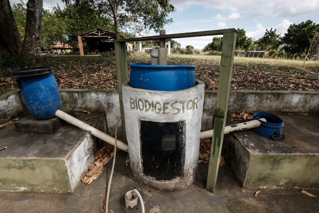 A biodigester is in an outdoor area under a blue sky with a few clouds. The cement base has a blue box attached on top, and white pipes that interconnect the other two blue boxes. In the background, there is a plot with some trees and leaves on the ground.