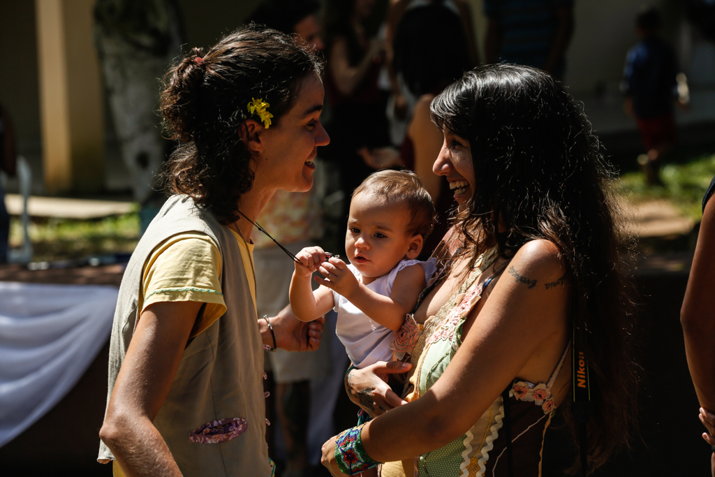 Two women are talking and facing to each other. The woman on the left, has short dark hair with a small yellow flower attached to her ear. She wears a yellow T-shirt and a beige vest over it. The other woman has dark long straight hair, a tattoo on her shoulder, and a sleeveless top. She carries a child in her lap, who holds a necklace attached to the neck.