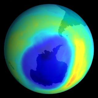 Planeta Terra, representada por um globo em diferentes cores brilhantes - amarelo, verde, azul claro e azul escuro. Uma bolha azul mais escura e disforme aparece quase no centro da imagem, representando o buraco na camada de ozônio sobre a Antártida.