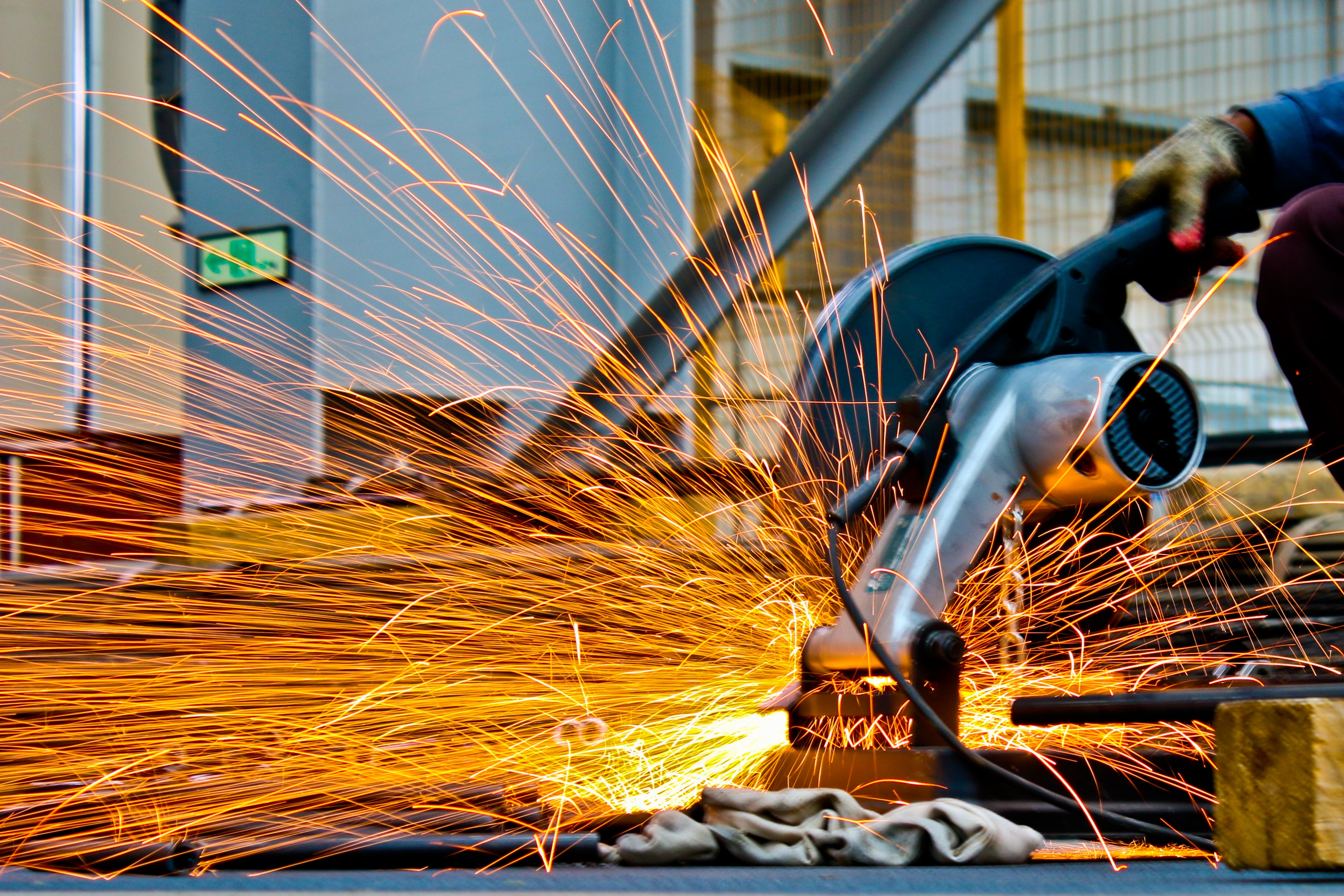 Close-up of an industrial machine, creating sparks as it cuts through metal.