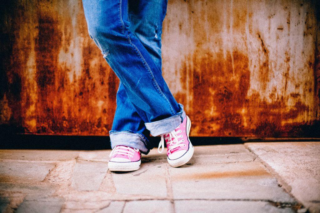 A imagem enquadra as pernas e os pés de um jovem, que usa calça jeans azul com a barra dobrada e um tênis rosa com cadarços brancos. O chão é cinza, com piso quadriculado irregular e a parede atrás do jovem é marrom desbotada.