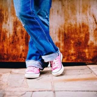 The legs and feet of a young person wearing blue jeans and pink sneakers with white laces. The floor is gray, with broken tiles. In the background, a rusting wall.