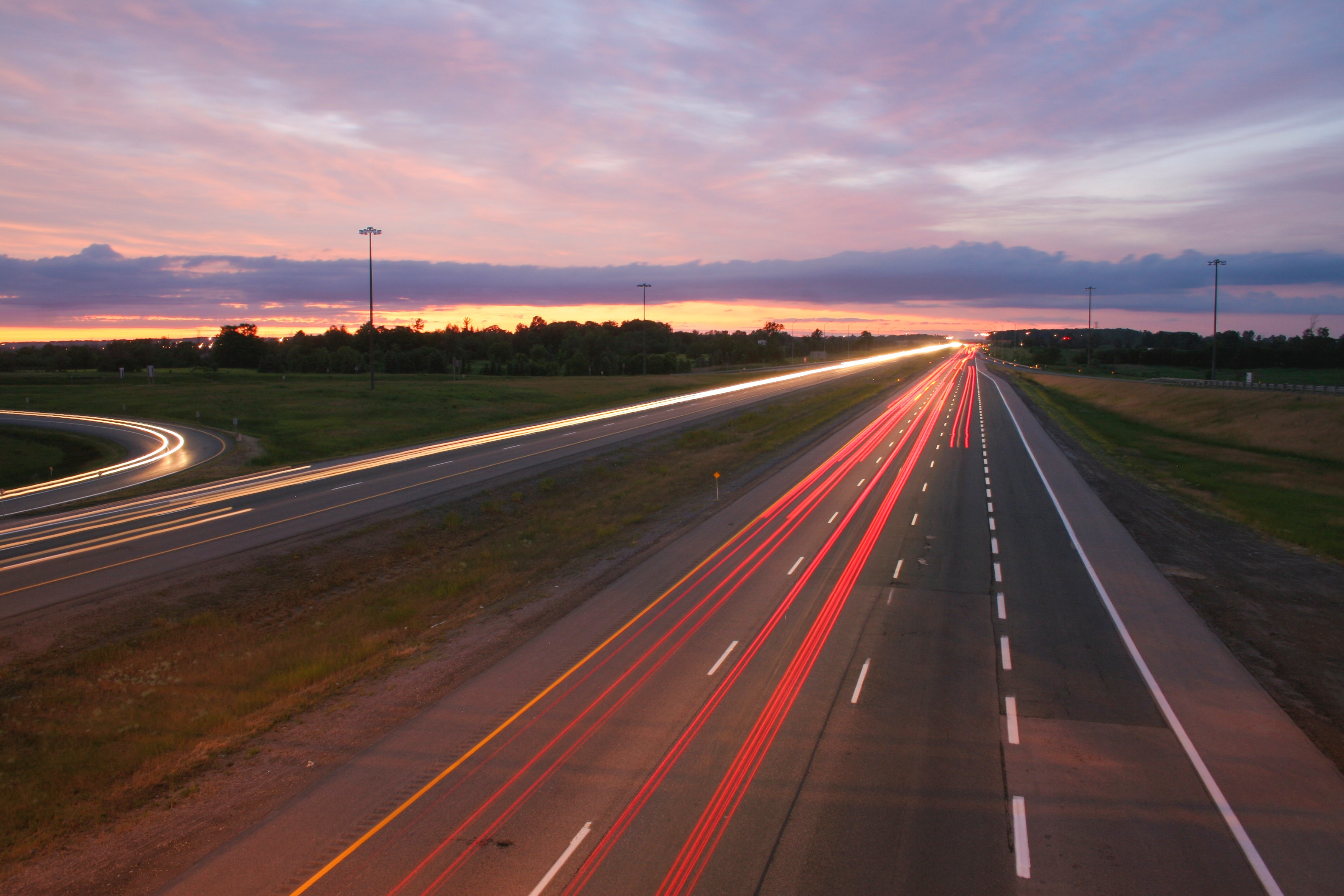 - A highway with streams of red and orange lights. It is dusk, with a dark blue and pink sky and some yellow light from the setting sun.