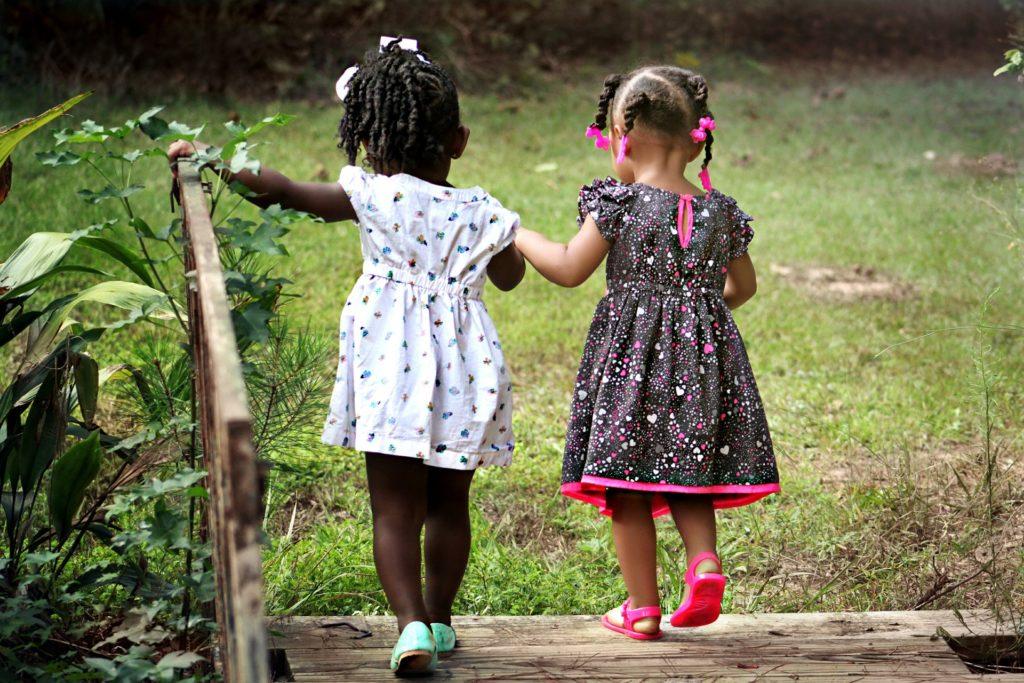 Dos niños pequeños están de la mano, de espaldas a la imagen. Pasan por un pequeño puente de madera hacia un verde césped. A la izquierda, la niña negra tiene el pelo oscuro sostenido con una cola de caballo, con una cinta blanca en la parte superior. Ella lleva un vestido blanco con pequeños estampados y zapatos color verde agua. Está con el brazo izquierdo extendido, en la barandilla de la pasarela. A su lado, la niña tiene el pelo dividido en partes, con trenzas y una cinta rosa en el extremo de cada una. Lleva un vestido negro, con pequeños estampados en rosa y blanco, con el dobladillo rosa y zapatos en el mismo tono.