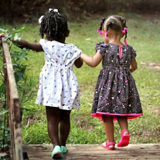 Two small, black girls are holding hands, their backs to the camera. They're crossing a small, wooden bridge onto a green lawn. The darker-skinned girl, who is on the left side, has her hair tied into a ponytail, with a white ribbon on top. She wears a white dress with a colorful pattern, as well as pale green shoes. Her left arm is outstretched. Her companion, to her right, is a lighter-skinned black child whose hair is divided into braids, a hot pink ribbon-shaped barrette on the end of each one. She wears a black dress with a pink and white pattern, and pink trim. Her shoes are also pink. The pink in the barrette, dress and shoes is the same shade.