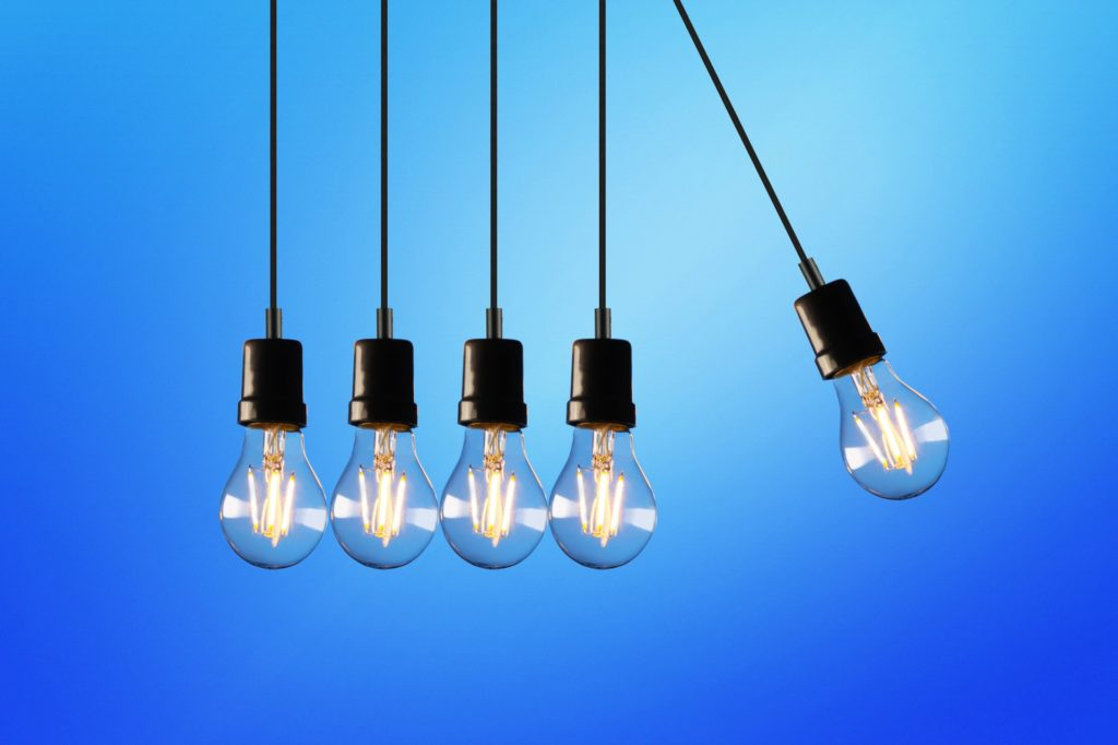 Five light bulbs hang by a cable against a background of blue sky.