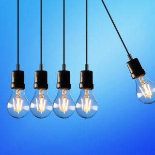 Imagem de três lâmpadas de luz com o fundo de um céu azul atrás. As lâmpadas estão penduradas pelo cabo, mas a imagem não mostra onde.