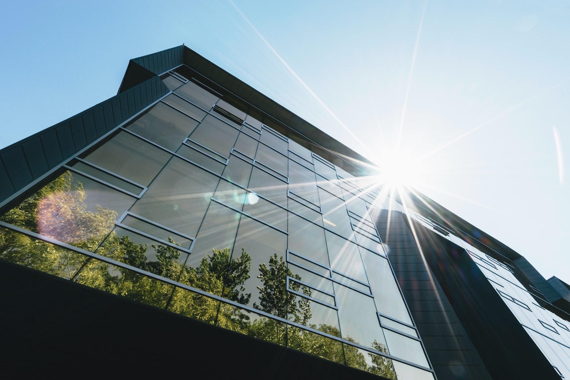 Primer plano de un edificio espejado en el que se reflejan árboles con sus copas llenas de hojas. En el techo del edificio inciden los rayos del sol.