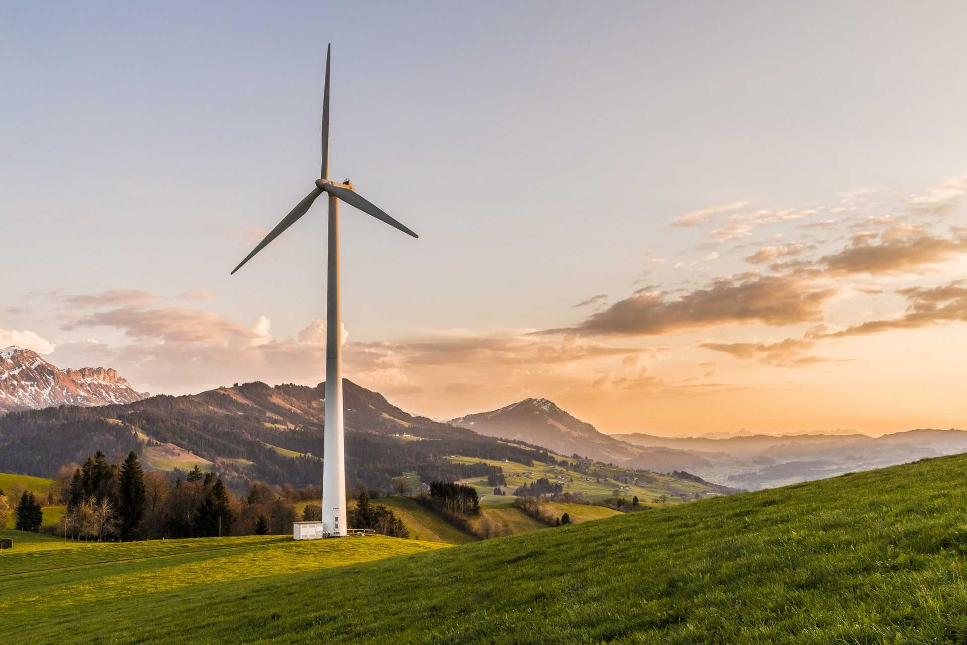 A tall wind turbine in the middle of a grassy field. In the background are some mountains, some of them covered in snow. The sky is yellow, with a few clouds.