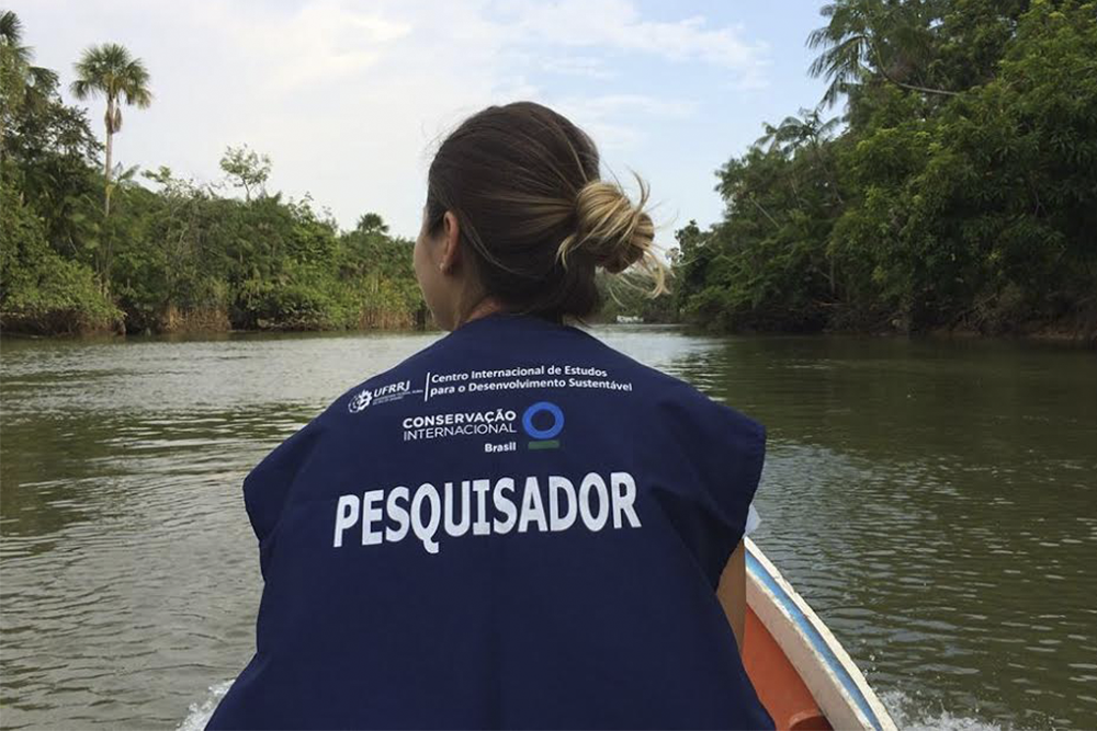 """A white woman sits with her back to the camera, her hair tied in a knot, wearing a blue Conservation International vest, with the word """"researcher"""" written in Portugues in white letters on its center. She is on a small boat going down a river. Strips of forest can be seen on either edge of the river."""