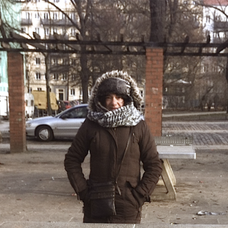 A white-skinned woman is wearing a heavy brown winter coat, a black and white scarf and a hat. She is in the center of the photo and is looking at the camera. The image shows her from the knees up. In the background is an urban area: brick columns, a parked car and some trees.