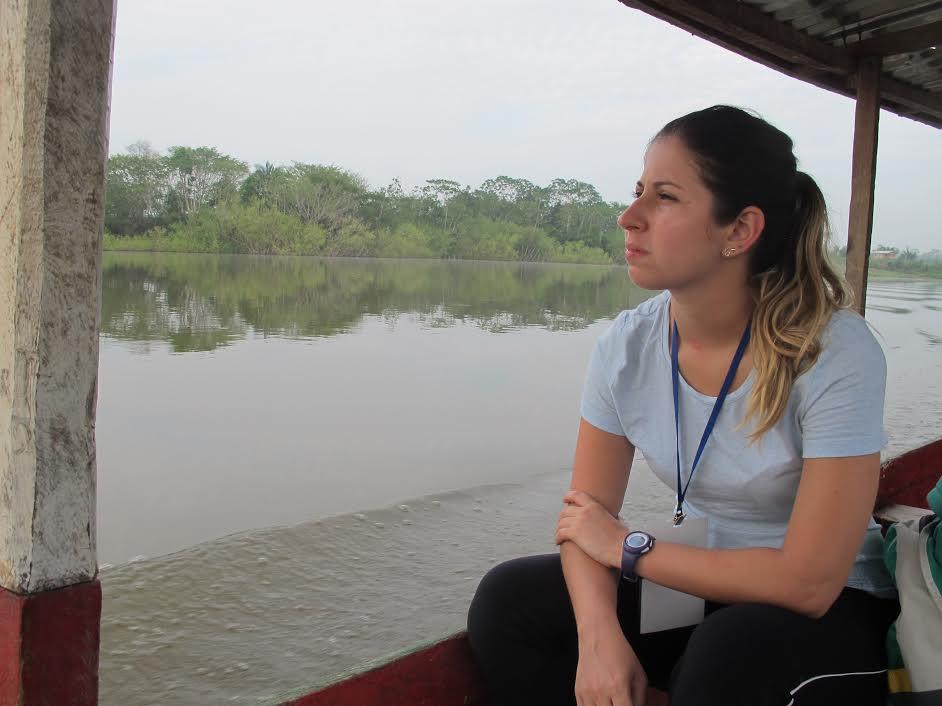 Uma mulher jovem, aparentando 20 e poucos anos, loira de cabelos presos, veste uma camiseta cinza e uma calça preta. Ela está sentada na beira de um barco, observando o rio e a paisagem verde ao redor